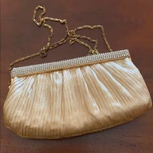 Jeweled, gold evening bag with chain.